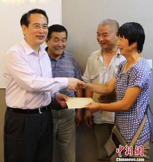当地时间8月15日,中国国务院侨办副主任谭天星(左一)代表国侨办向当地困难华侨华人代表发放慰问金。 王修君 摄