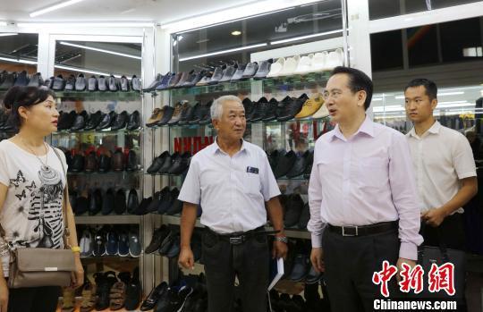 当地时间8月15日,中国国务院侨办副主任谭天星(右二)率代表团走访了哈巴罗夫斯克中国商人集中的维宝大市场,详细了解了中国商人们的生活、经营环境和当前所面临的困难。 王修君 摄