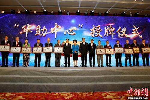 """9月29日,国务院侨办主任裘援平(左八),党组书记、副主任许又声(左九)、副主任谭天星(左七)、副主任郭军(左十)为第四批15家""""华助中心""""授牌。当日,中国国务院侨务办公室、中国海外交流协会在北京举办""""为侨服务日""""活动,来自83个国家和地区的537位侨界代表及国内相关部门负责人共庆中华人民共和国成立68周年。中新社记者 李慧思 摄"""
