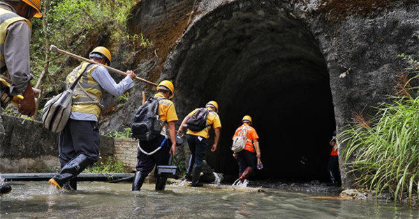 Workers patrol tunnel to ensure railway safety during flood season