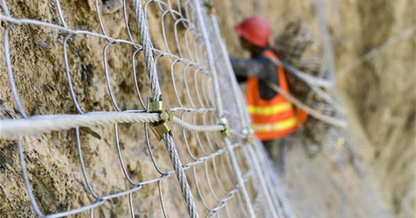 Men work on the cliff in China's Xinjiang