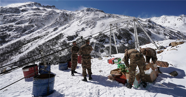 Soldiers transport goods through ropeways in Tibet's snow-capped mountainous area