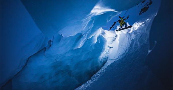Daredevil snowboards in narrow ice cave