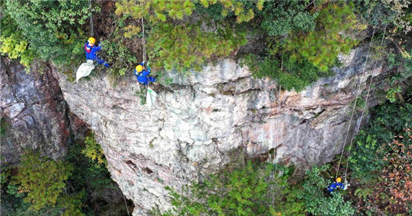 Blue Sky rescue team clean garbage on cliff in Zhangjiajie