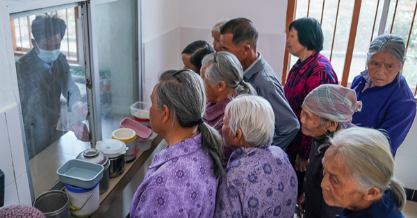 Elderly people receive free lunch from village canteen