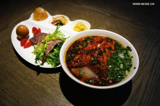 Photo taken on April 12, 2017 shows a package meal of beef noodle at a noodle restaurant in Lanzhou, capital of northwest China's Gansu Province. As a piece of name card of Lanzhou City, beef noodle is an indispensable food of local people. There are more than 1,000 beef noodle cookshops in Lanzhou and they can sell over one million bowls of beef noodle every day.  (Photo/Xinhua)