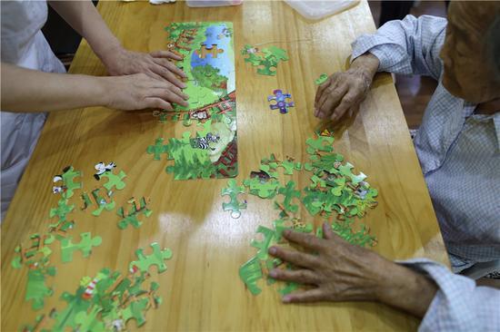 Seniors at Songtang play with a jigsaw puzzle. (Photo: China Daily/Wang Jing)