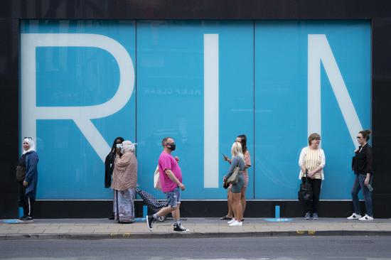 People queue outside a Primark store in central Manchester, Britain, June 15, 2020. (Photo by Jon Super/Xinhua)