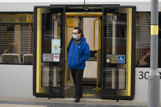 A man wearing a mask gets off a tram at Manchester Victoria Railway Station in Manchester, Britain, on June 15, 2020. (Photo by Jon Super/Xinhua)■