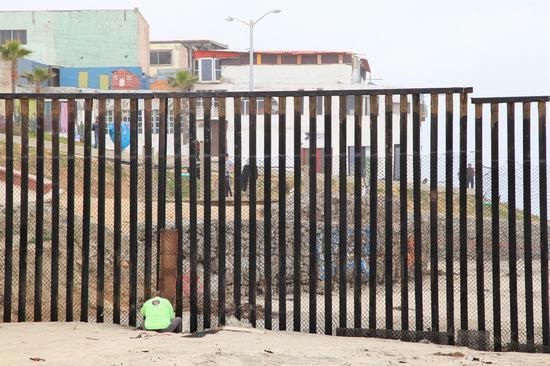 2018年4月30日,一名工人在美国圣地亚哥修理美国和墨西哥之间的边界墙。(新华社/黄衡)