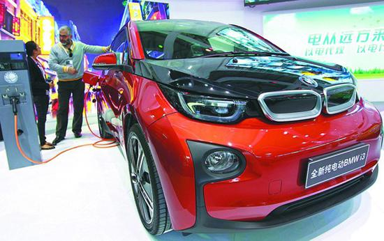 A representative shows how to charge up a BMW i3 electric car at an auto show in Shanghai. (Photo/Xinhua)
