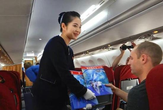 A crew member shows a magazine to a foreign journalist on a plane carrying reporters to the DPRK to watch the closure of a nuclear site on May 22, 2018. /CCTV Photo