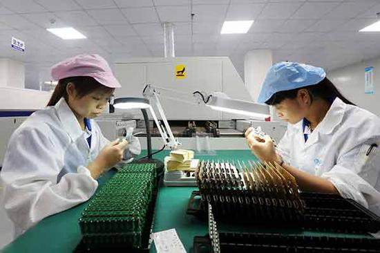 Technicians check chips at a technology company in Guigang, the Guangxi Zhuang autonomous region. (Photo by Tan Kaixing/for China Daily)