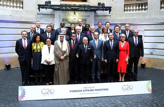 State Councilor and Foreign Minister Wang Yi, left of Australia's Julie Bishop, attends the G20 Meeting of Foreign Affairs Ministers in Buenos Aires, Argentina, on Monday with other foreign ministers. He called for boosting multilateralism and the G20's role in global governance in a speech.(Photo/Xinhua)