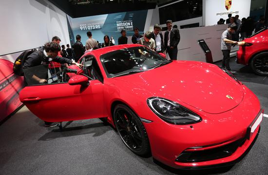 Visitors look at a Porsche during the biennial Beijing auto show in May. (Photo by Wang Zhuangfei/China Daily)