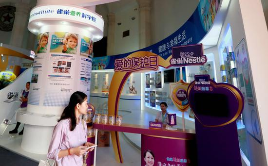 A visitor walks past Nestle's booth at an exhibition of dairy products held in Beijing. (Photo provided to China Daily)