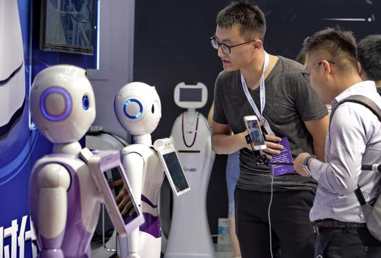Multi-functional robots developed by iFlytek Co Ltd are displayed at the 2017 World Robot Conference in Beijing. (Photo/Xinhua)