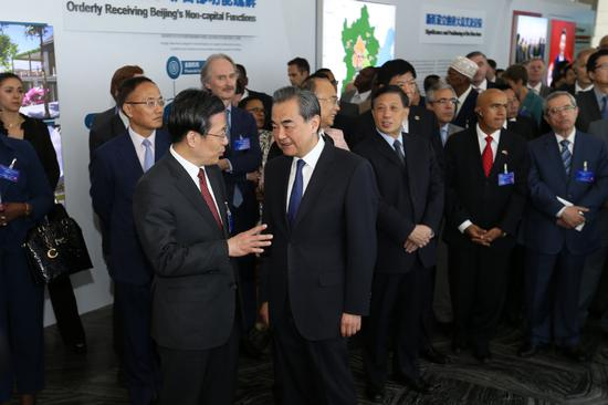 State Councilor and Foreign Minister Wang Yi (center) tours exhibitions promoting Xiongan New Area on Monday at the Foreign Ministry in Beijing with foreign diplomats based in the Chinese capital. Wang said Xiongan will be a role model of China's high-quality development.  (Photo by Wang Zhuangfei/China Daily)