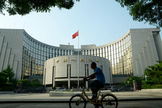 A cyclist pedals past the headquarters of the People's Bank of China in Beijing.  (Photo by Fan Shaoguang/For China Daily)