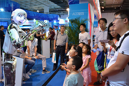 Delighted children and adults watch the performance of a robot at the 2017 China Beijing International High-Tech Expo on June 8. (Photo/China Daily)