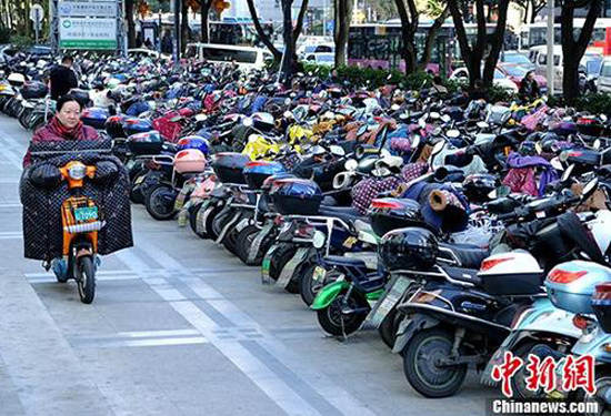 A woman rides an electric bike in Beijing. (Photo/China News Service)