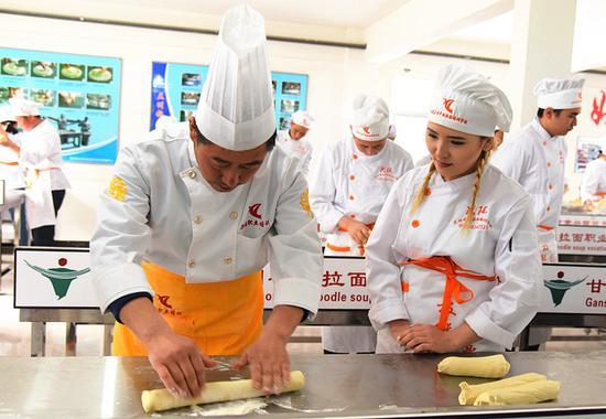 A chef shows a student how to flatten dough using a rolling pin at the school. (Photo: Xinhua/Wang Peng)