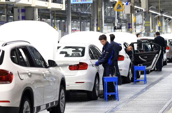 Employees work on the production line of a BMW joint venture in Shenyang, capital of Liaoning Province. (Photo/Xinhua)