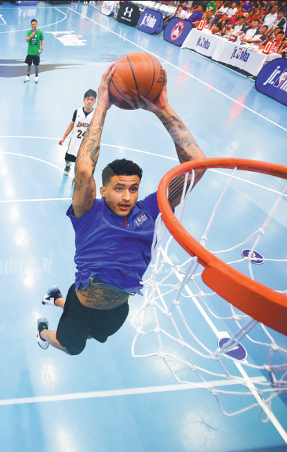 Kyle Kuzma of the Los Angeles Lakers shows Chinese students  how it's done during an NBA Cares clinic, which took place on  the sideline of the Jr. NBA Beijing High School League Finals at  the Affiliated High School of Peking University in Beijing on  Saturday. (Photo/Provided to China Daily)