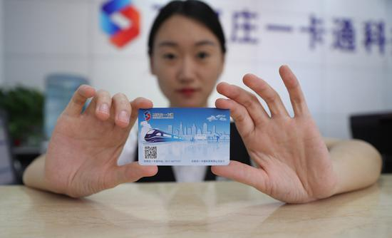 A worker shows a new transit card in Shijiazhuang, Hebei Province, on June 4, 2018. (Photo/Xinhua)
