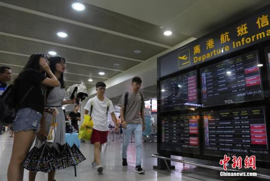 Passengers check information at the Sanya Phoenix International Airport, Hainan Province.  (Photo/China News Service)