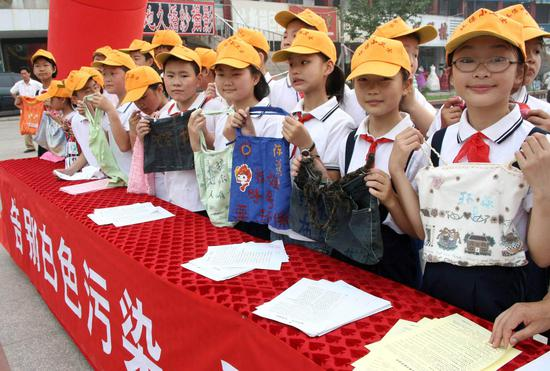 File photo taken on June 1, 2008 shows pupils displaying hand-made shopping bags in Hanshan, a county of east China's Anhui Province. (Xinhua/Cheng Qianjun)