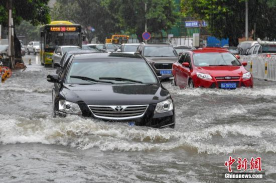 Vehicles run on a flooded street in Haikou, south China's Hainan Province, on June 6, 2018. (Photo: China News Service/Luo Yunfei)
