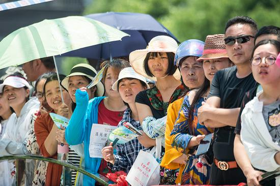 Parents and family members await students outside the entrance to an examination site in Haian, Jiangsu Province, during the annual national college entrance exams on Thursday. It was the first of two days of testing across the country. (Xu Jinbai/For China Daily)