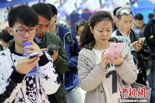 People read information on their mobile phones. (Photo/China News Service)