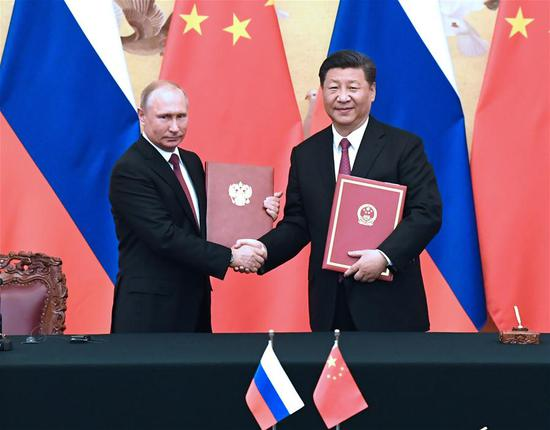 Chinese President Xi Jinping and his Russian counterpart Vladimir Putin sign a joint statement after their talks in Beijing, capital of China, June 8, 2018. (Xinhua/Rao Aimin)