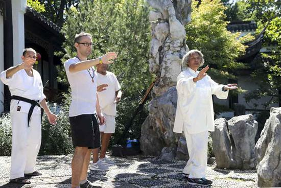 People learn to practise Tai Chi at Chinese Scholar's Garden in New York, the United States, on Sept. 23, 2017. The annual Asian-themed festival features activities including performances of Asian music and dance, demonstrations of martial arts, lessons in Chinese calligraphy was held at Chinese Scholar's Garden to celebrate the Autumn Moon Festival on Saturday. (Xinhua/Wang Ying)