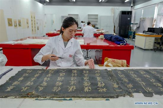 A staff worker repairs a calligraphy collection at a hospital for conservation in the Palace Museum in Beijing, capital of China, June 9, 2018. The hospital for conservation opened to the public Saturday, as part of ongoing activities held for China's Cultural and Natural Heritage Day. The first visitors were a group of 40 people, who watched