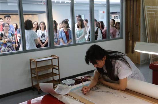 Visitors observe as a painting is repaired at the Palace Museum on Saturday, China's Cultural and Natural Heritage Day. (Photo by Jiang Dong/China Daily)