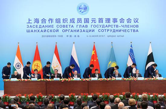 Leaders of SCO member states sign documents on Sunday. (Photo by Feng Yongbin/China Daily)