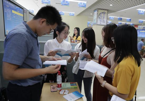 Job applicants (right) consult representatives of an employer at a job fair on the sidelines of the Straits Forum in Xiamen, Fujian province, on Saturday.  (Chen Lijie/For China Daily)