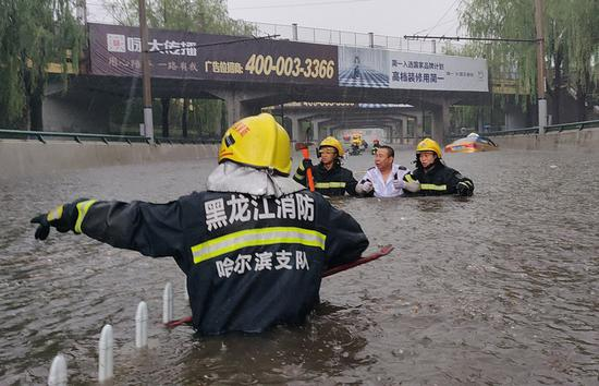 Firefighters evacuate people stranded by a sudden rainstorm on June 11, 2018 in Harbin, Heilongjiang Province. (Photo by Xiao Jinbiao / For China Daily)