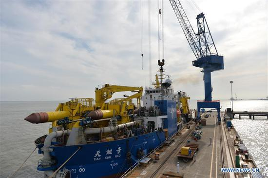 Tian Kun Hao, a Chinese-built dredging vessel, the largest of its kind in Asia, berths at a port in Qidong City, east China's Jiangsu Province, June 7, 2018. Tian Kun Hao, constructed by Tianjin Dredging Co. Ltd., a subsidiary of China Communication Construction Co., Ltd. (CCCC), finished its first sea trial. The 140-meter-long vessel, with the designed capacity to dredge 6,000 cubic meters per hour, can dig as deep as 35 meters under the sea floor. (Xinhua/Mao Zhenhua)