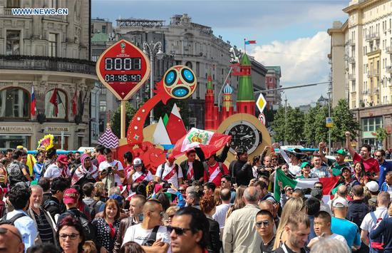 Fans cheer in front of a countdown clock near the Red Square in Moscow, Russia, on June 13, 2018. The 2018 Russia World Cup will kick off on June 14. (Xinhua/Yang Lei)