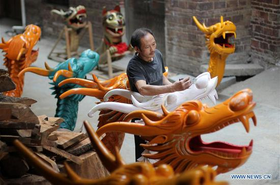 Chinese folk artist makes dragon head for bow of dragon boat