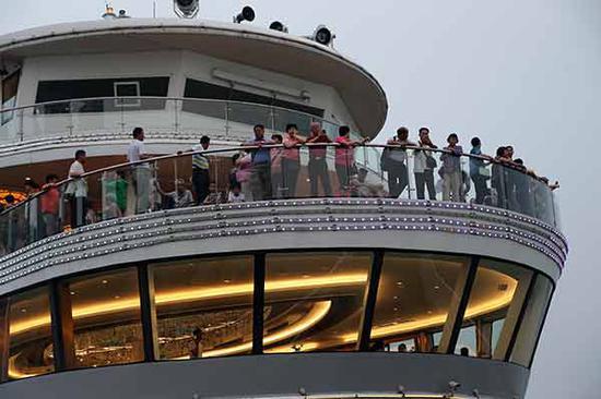 Tourists take in the sights as their cruiser navigates the Yangtze River. (Photo by Wang Zhuangfei/China Daily)