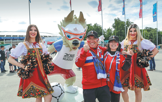 A Chinese couple from Jiangxi province say they are excited about attending World Cup matches as they pose with a mascot in Moscow on Thursday. (Photo/Xinhua)