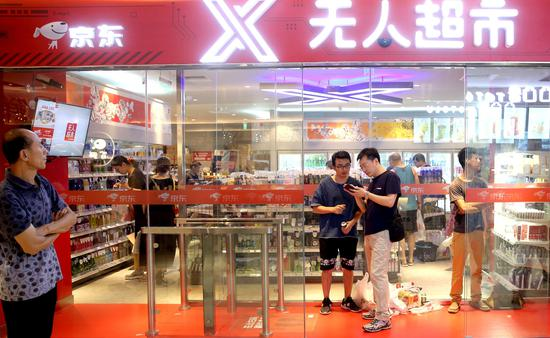 Shoppers at an unmanned supermarket of JD in Beijing. (Photo by Wang Jing/China Daily)