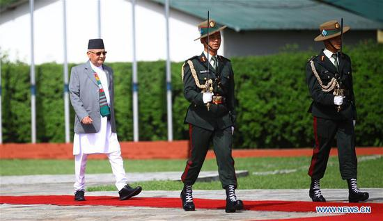 Nepalese Prime Minister Khadga Prasad Sharma Oli (L) reviews the honor guard as he left for China at Tribhuvan International Airport in Kathmandu, capital of Nepal, June 19, 2018. Khadga Prasad Sharma Oli started a six-day visit to China on Tuesday. (Xinhua/Sunil Sharma)