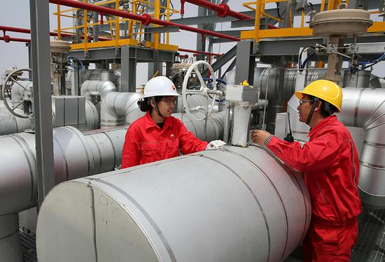 Technicians check liquefied natural gas facilities in Nantong, Jiangsu province. (Photo by Xu Congjun/For China Daily)