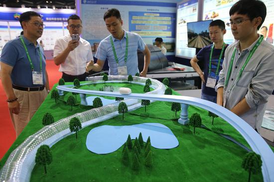 Visitors observe the model of a superconducting tube maglev at the 2018 World Transport Convention in Beijing, June 19, 2018. (Photo/China Daily)